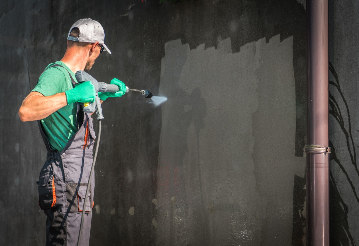 a man pressure cleaning a wall